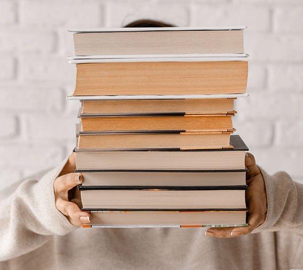 Bücherstapel wird in die Kamera gehalten | deinestarkeseite.de
